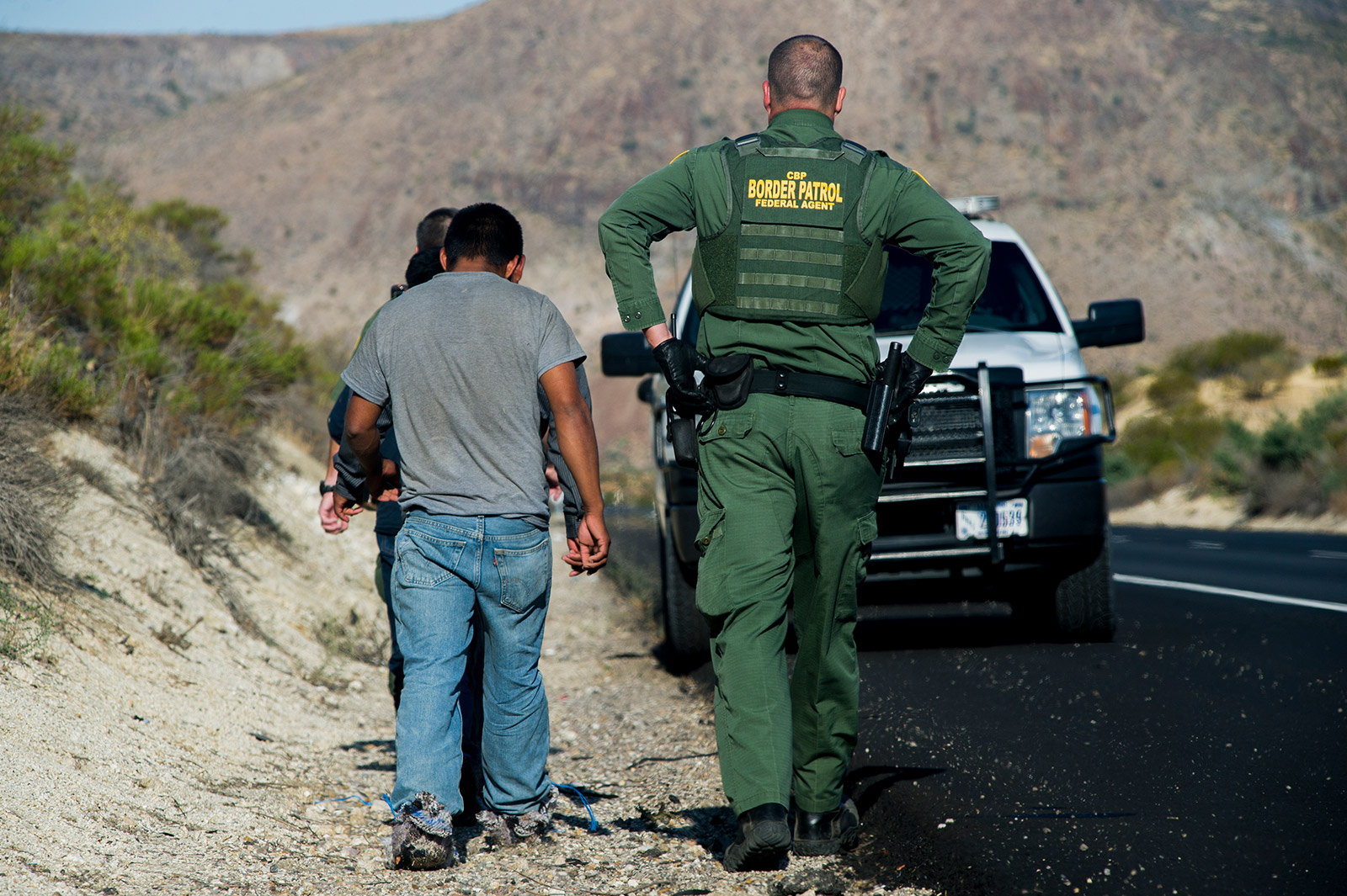 A Border Patrol agent detains three men along Interstate 8 near the U.S.-Mexico border in eastern San Diego County on Sept. 5, 2017. The men are suspected of entering the U.S. illegally and were stopped when agents saw them entering a vehicle near the border. <em>(Brandon Quester/inewsource)</em>