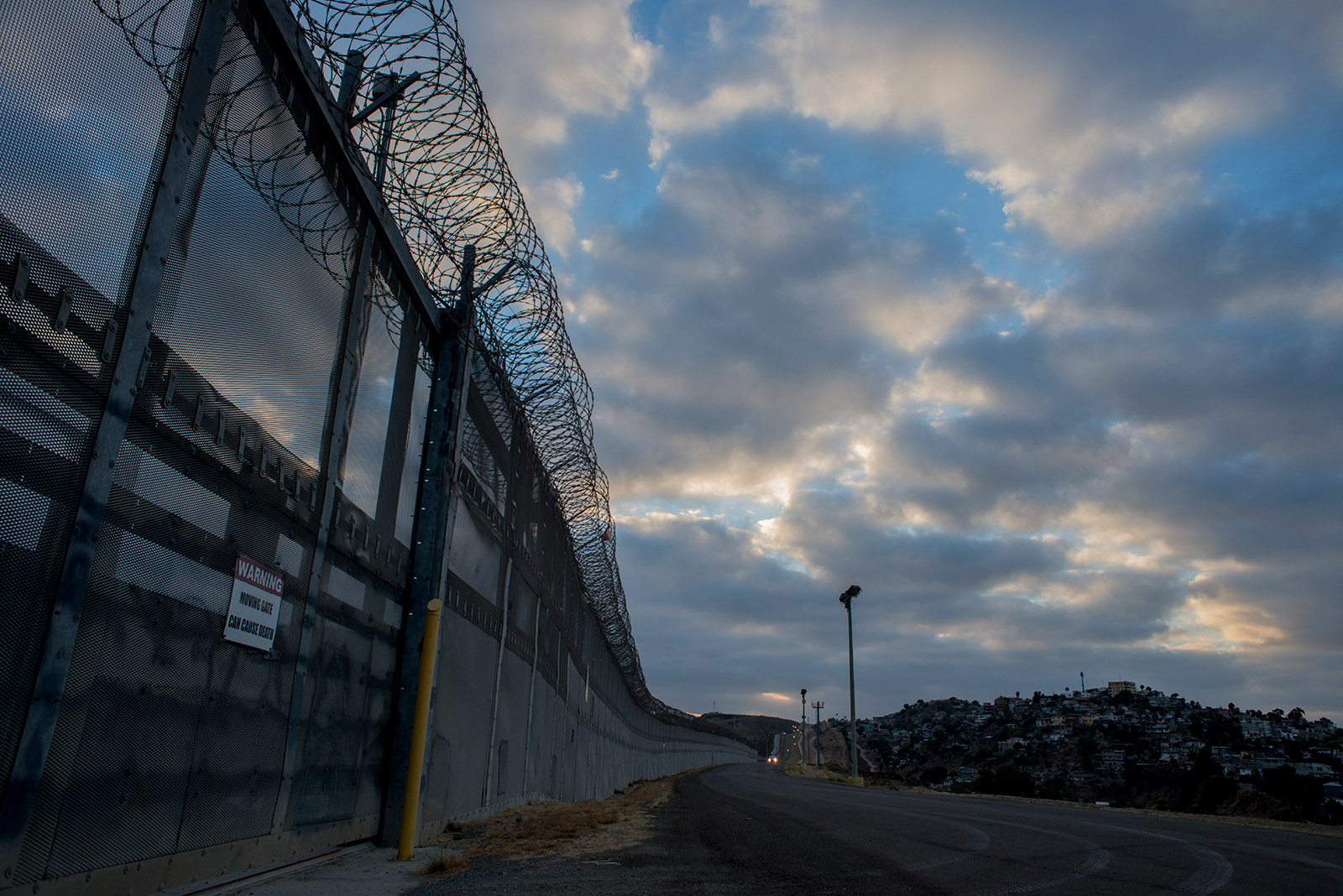 Stretches of secondary fencing are topped with spirals of concertina wire along the U.S.-Mexico border between the San Ysidro and Otay Mesa ports of entry, in San Diego on Aug. 16, 2017. Border Patrol agents use the frontage road between this and primary fencing to patrol for immigrants attempting to enter the U.S. illegally. <em>(Brandon Quester/inewsource)</em>