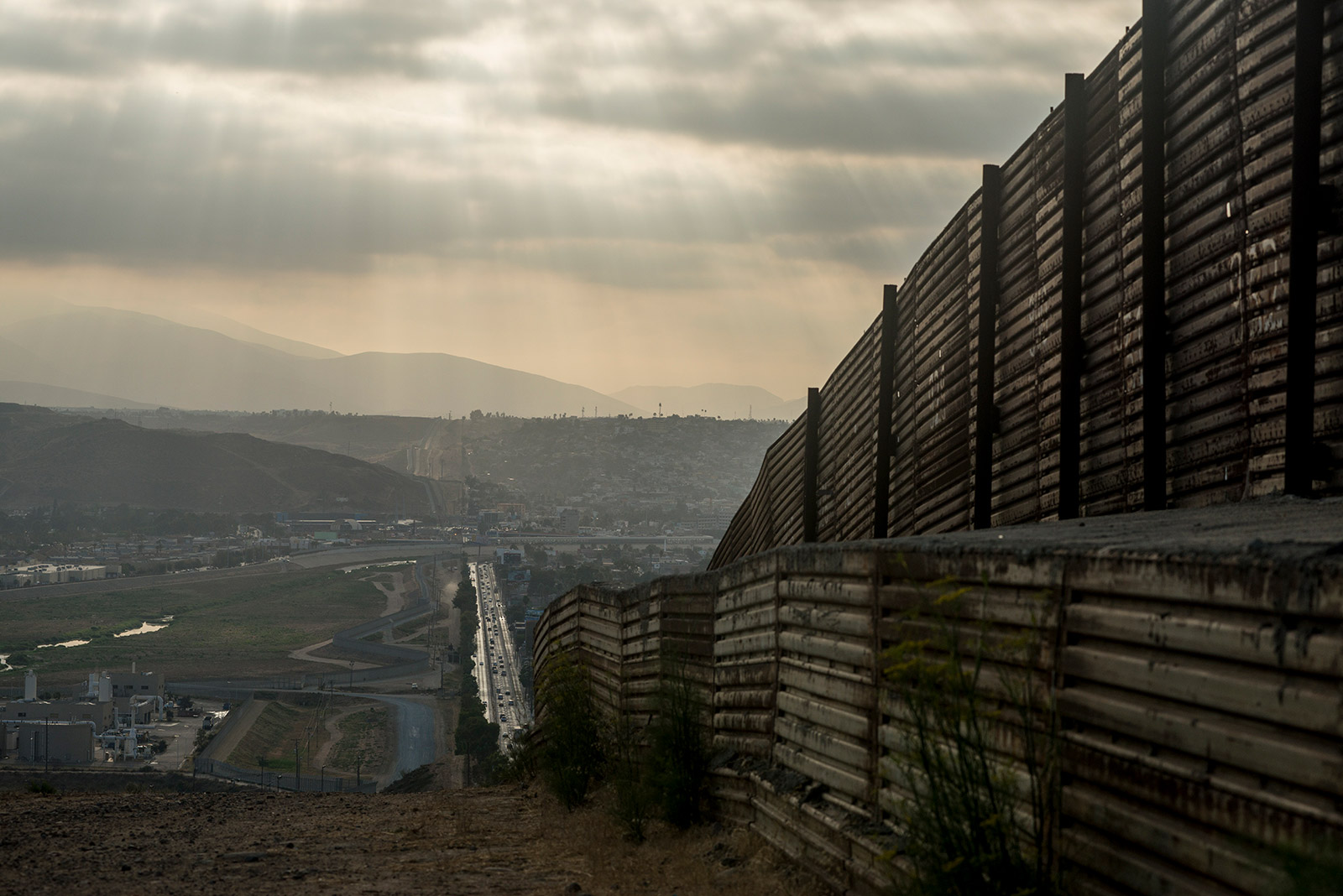 The majority of the primary fencing along the U.S.-Mexico border in San Diego is made of corrugated steel that once served as helicopter landing pads during the Vietnam War. This section, shown on Aug. 16, 2017, lines a hill leading west toward the San Ysidro Port of Entry. <em>(Brandon Quester/inewsource)</em>