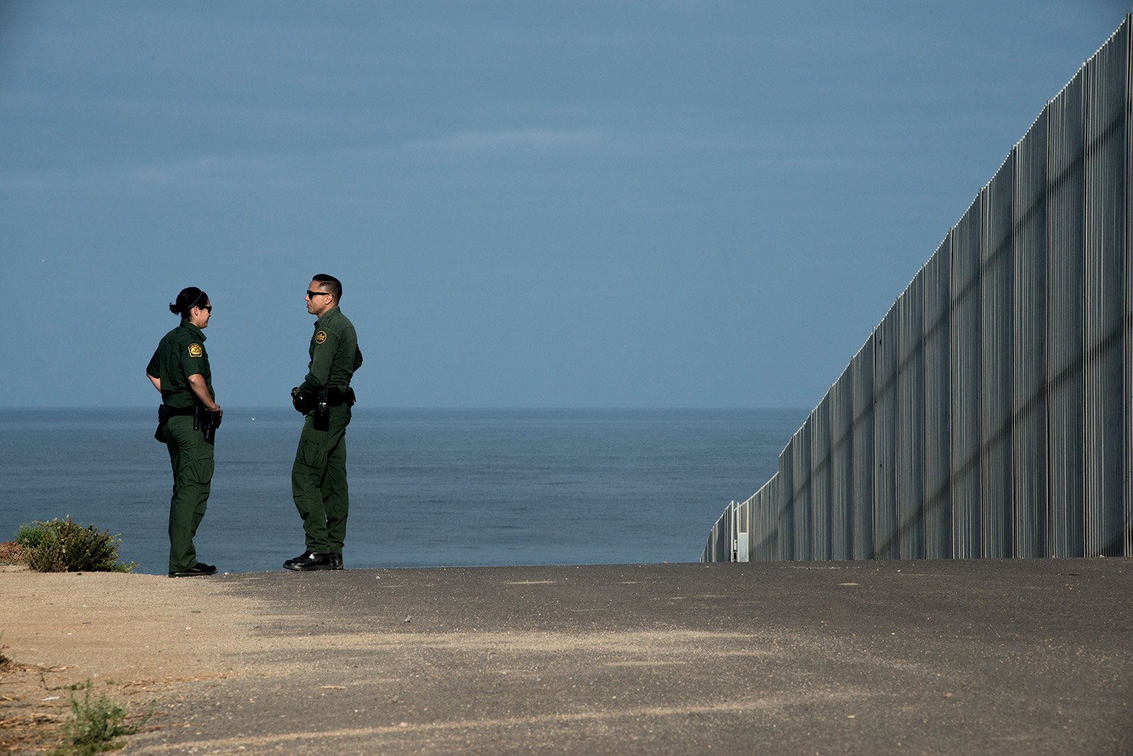 Border Patrol agents Eduardo Olmos, right, and Tekae Michael walk along the frontage road next to primary fencing along the U.S.-Mexico border in San Diego on Aug. 16, 2017. The section of fencing shown here is considered secondary and leads down to the Pacific Ocean. <em>(Brandon Quester/inewsource)</em>