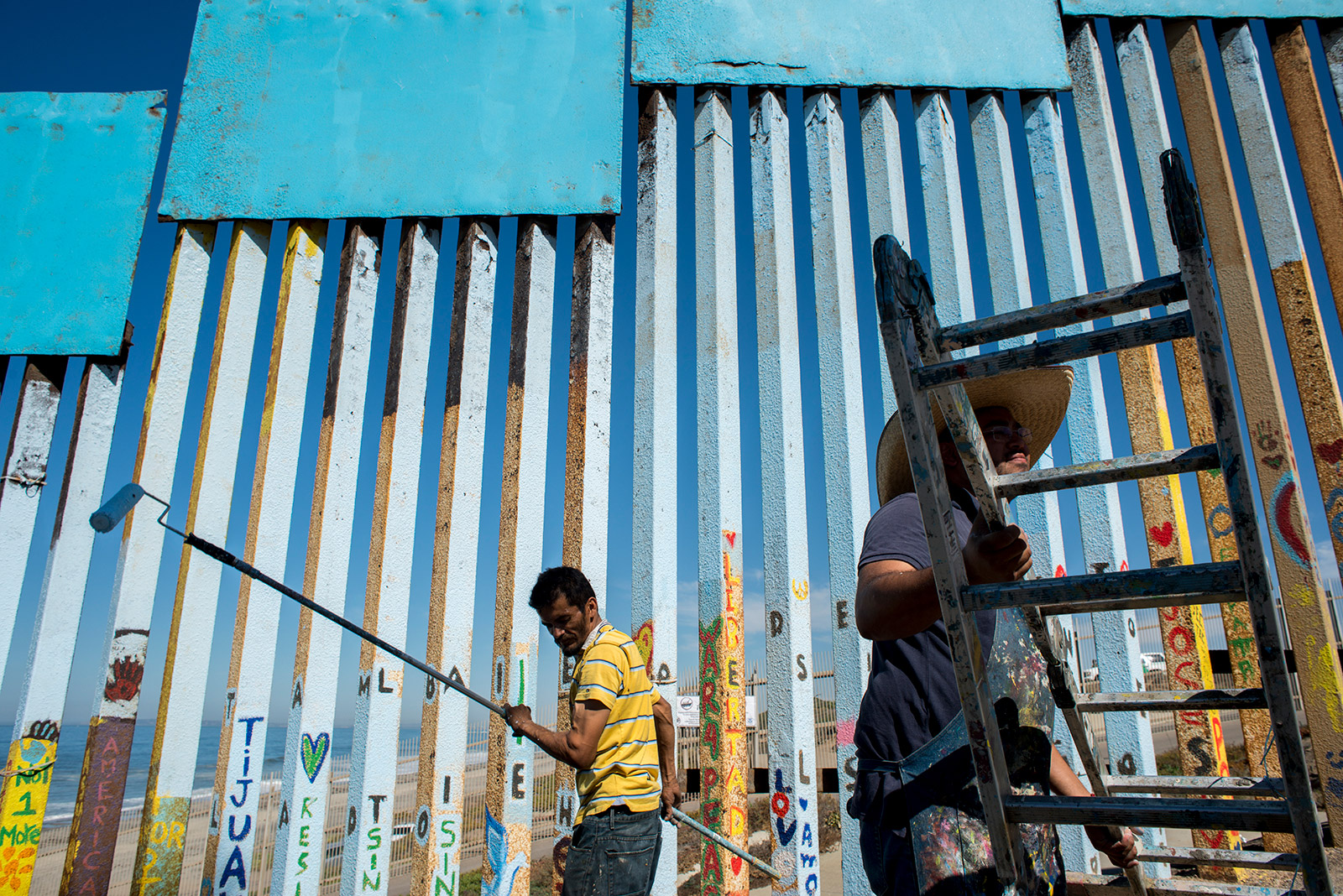 Sergio Tellez, left, volunteers with Enrique Chiu on Oct. 7, 2017, as they paint the easternmost edge of fencing along the U.S.-Mexico border in Tijuana. Tellez used a paint roller to help remove corroded metal from the fencing before adding a new layer of blue. <em>(Brandon Quester/inewsource)</em>