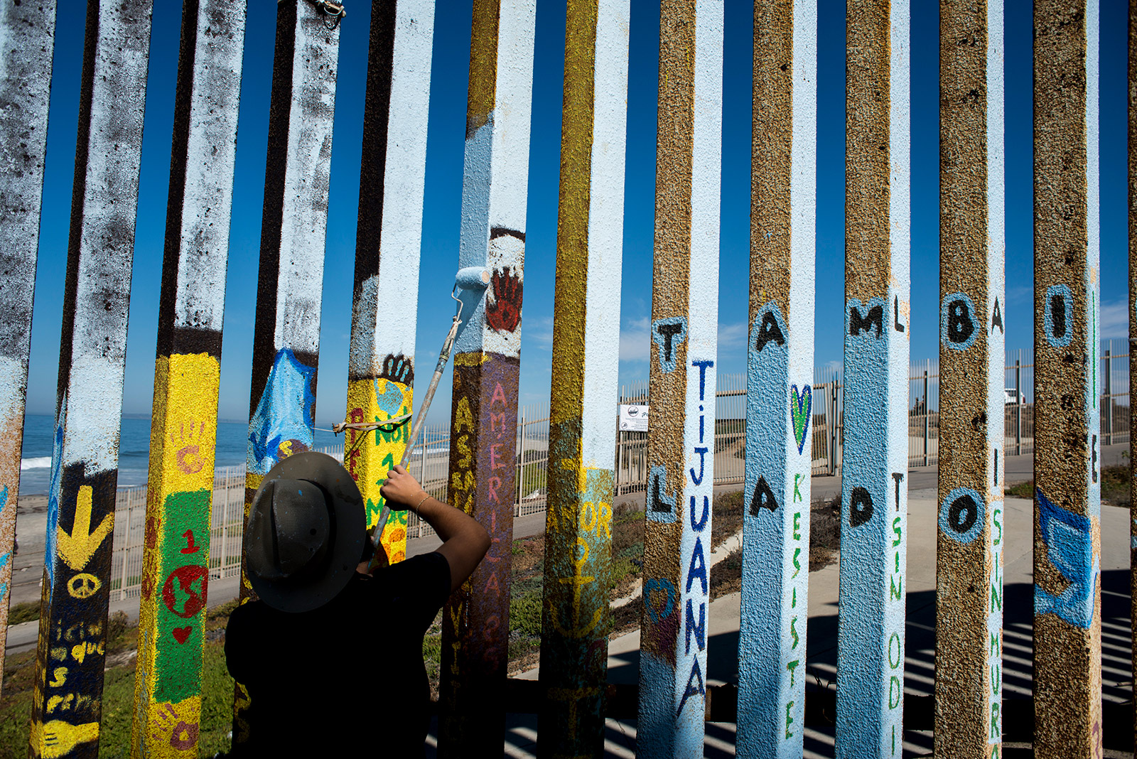 Luis Marmolejo volunteers with muralist Enrique Chiu on Oct. 7, 2017, to paint the far eastern edge of fencing along the U.S.-Mexico border. With the ocean less than 100 meters away from where the group was painting, Chiu said the saltwater quickly erodes the metal bars that separate the two countries. <em>(Brandon Quester/inewsource)</em>