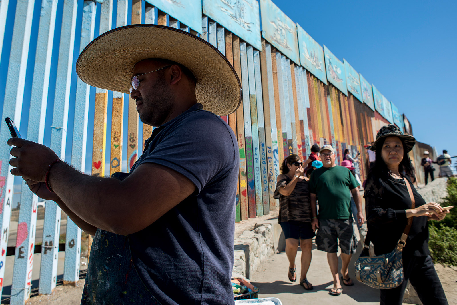 Enrique Chiu, a Tijuana-based muralist painting the U.S.-Mexico border fence, checks a phone message on Oct. 7, 2017, as tourists and visitors to Friendship Park in Tijuana walk by and watch. <em>(Brandon Quester/inewsource)</em>