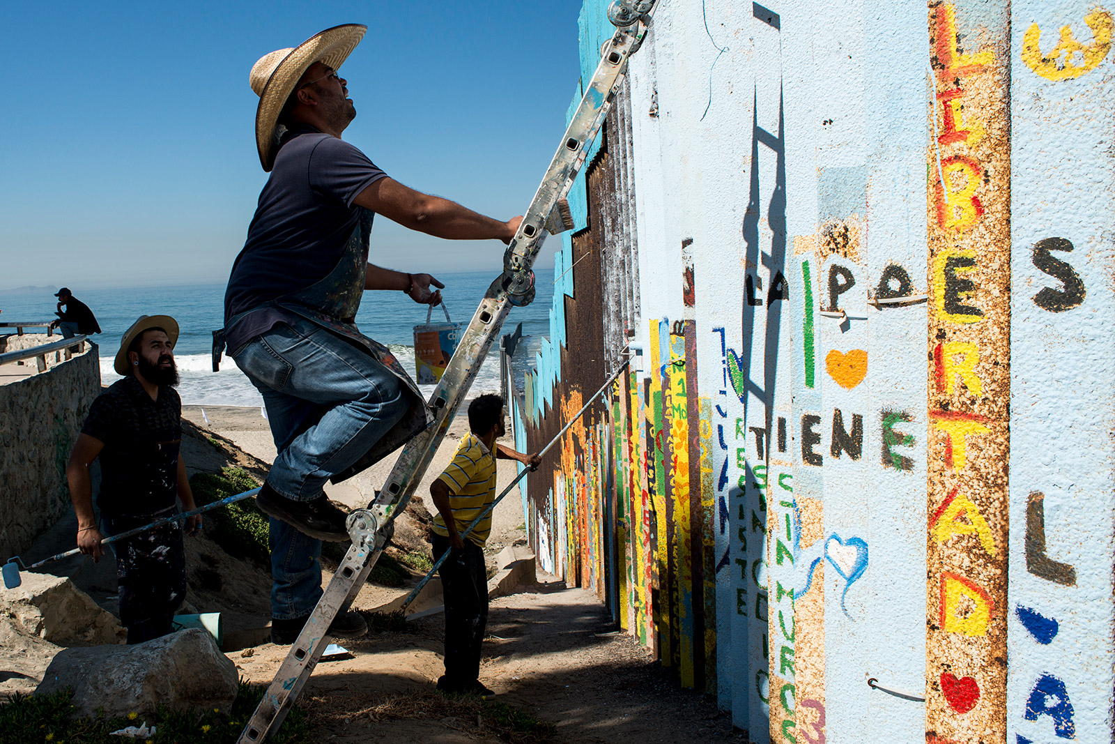 From left, Luis Marmolejo, Enrique Chiu and Sergio Tellez, begin painting sections of fencing along the U.S.-Mexico border at Friendship Park in Tijuana on Oct. 7, 2017. Chiu, a muralist, has worked for nearly a year to paint messages of hope in what could become the world's largest mural. <em>(Brandon Quester/inewsource)</em>