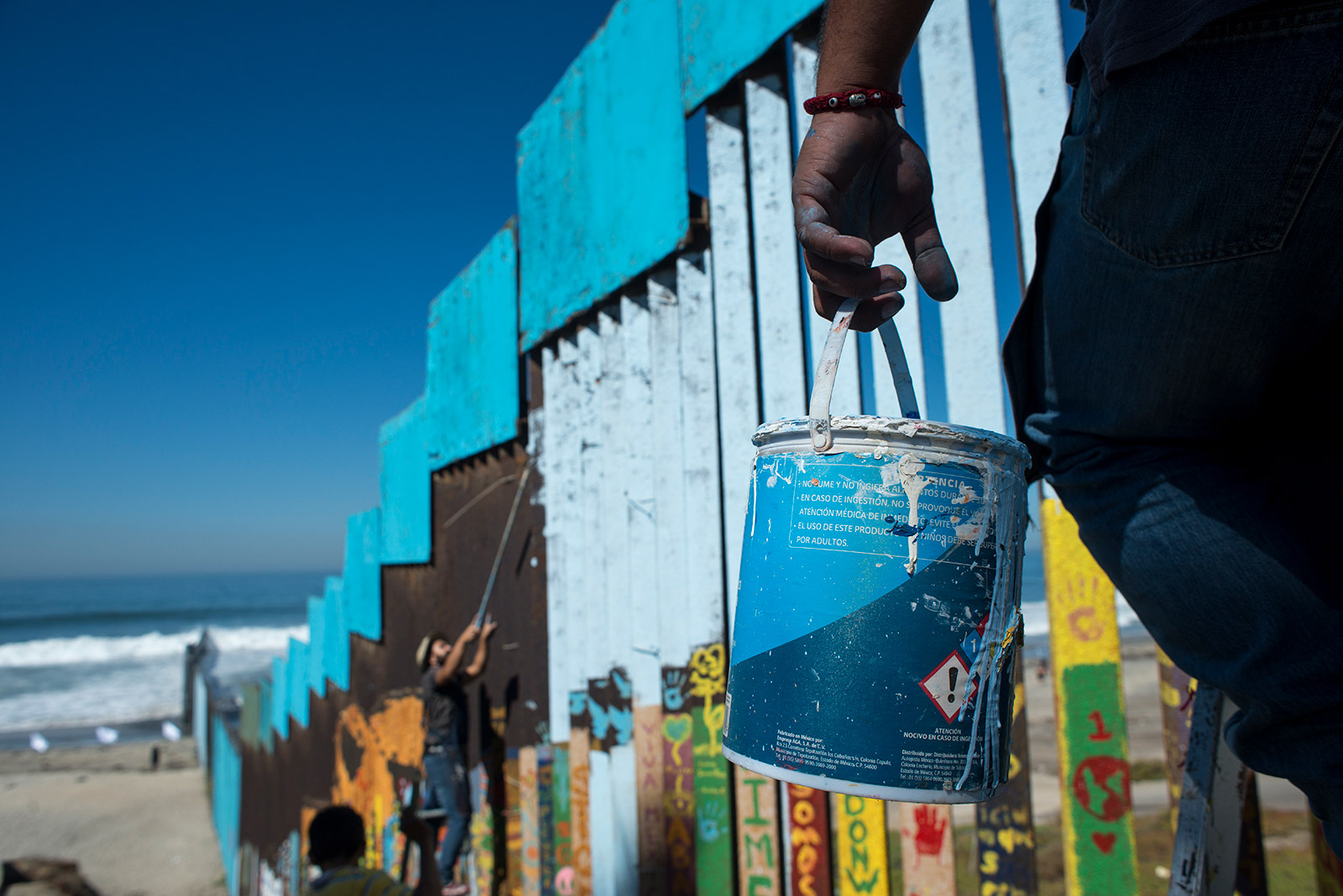 Enrique Chiu carries a can of blue paint up a ladder that leans against the U.S.-Mexico border wall at Friendship Park in Tijuana on Oct. 7, 2017. Chiu and two volunteers spent the day painting the section of the fence that leads into the Pacific Ocean. <em>(Brandon Quester/inewsource)</em>