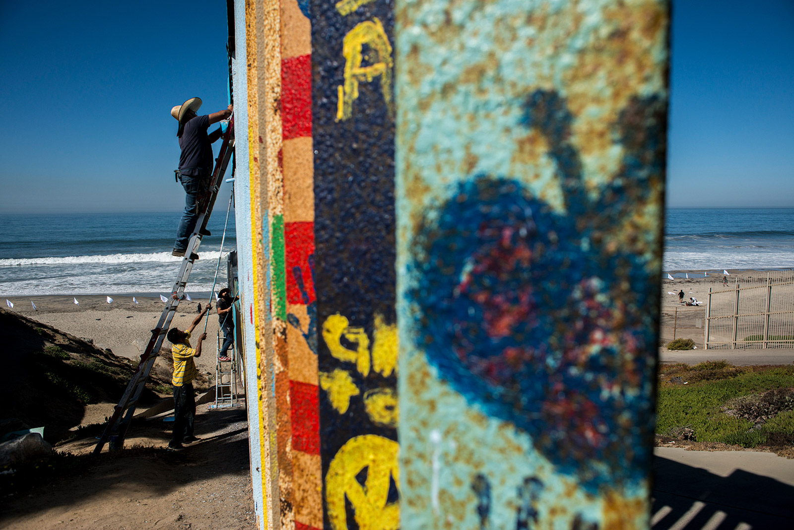 Separated by tall steel fencing, Enrique Chiu and two volunteers paint murals along the southern-facing section of fencing that separates the United States and Mexico on Oct. 7, 2017. This section, at Friendship Park in Tijuana, is the easternmost edge of the border that ends in the Pacific Ocean. <em>(Brandon Quester/inewsource)</em>