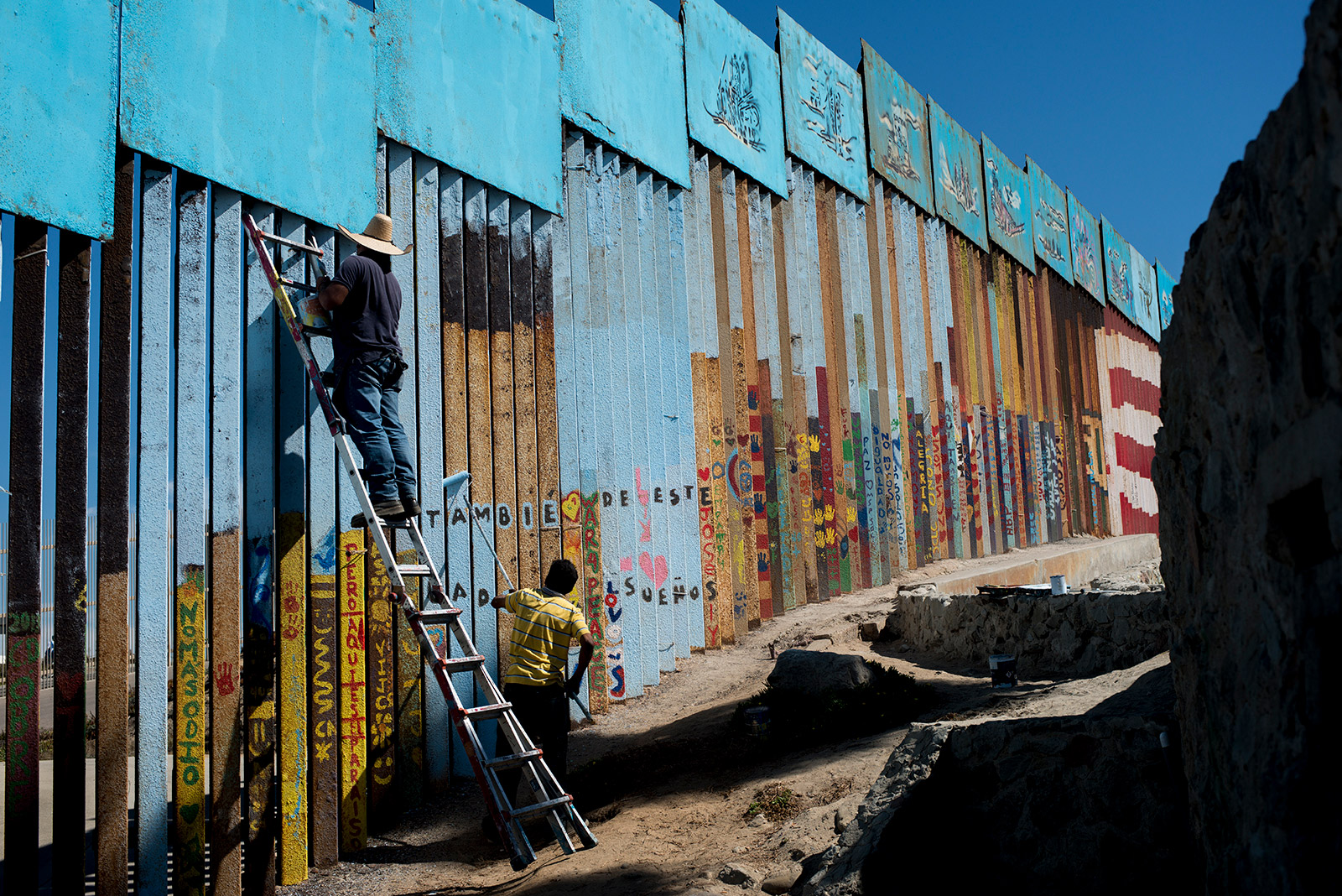Enrique Chiu stands on a ladder to paint the U.S.-Mexico border fencing at Friendship Park in Tijuana on Oct. 7, 2017. <em>(Brandon Quester/inewsource)</em>