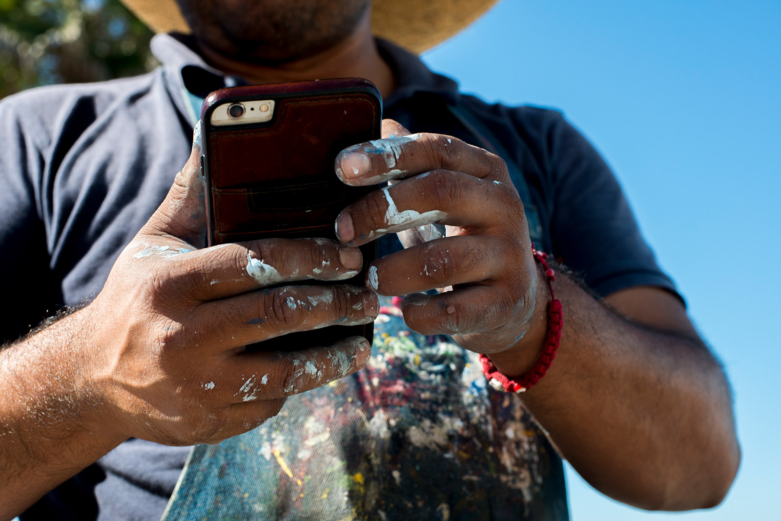 Enrique Chiu, a Tijuana-based muralist, checks his phone with paint-stained hands while taking a break from his work at Friendship Park in Tijuana on Oct. 7, 2017. <em>(Brandon Quester/inewsource)</em>