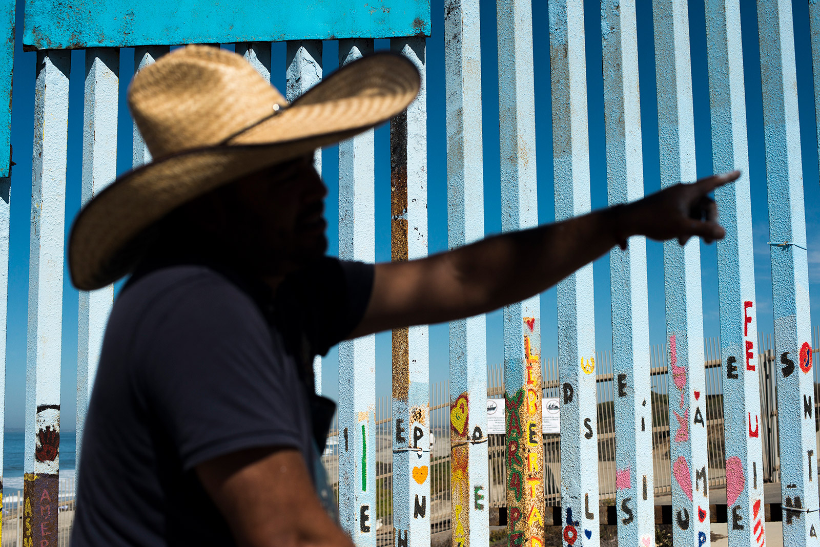 Enrique Chiu, a Tijuana-based muralist, is silhouetted against the fencing of the U.S.-Mexico border on Oct. 7, 2017. Chiu has worked for nearly a year painting murals along the fencing that separates San Diego and Tijuana. <em>Brandon Quester/inewsource</em>