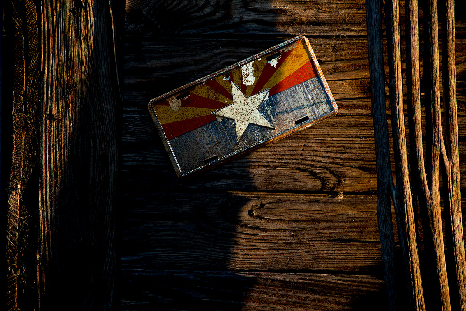 An Arizona license plate is nailed to the wall of a small barn outside Ajo, Arizona, on Aug. 25, 2017. The barn is used Aguilas Del Desierto, a group that searches for lost migrants in the desert. <em>(Brandon Quester/inewsource)</em>