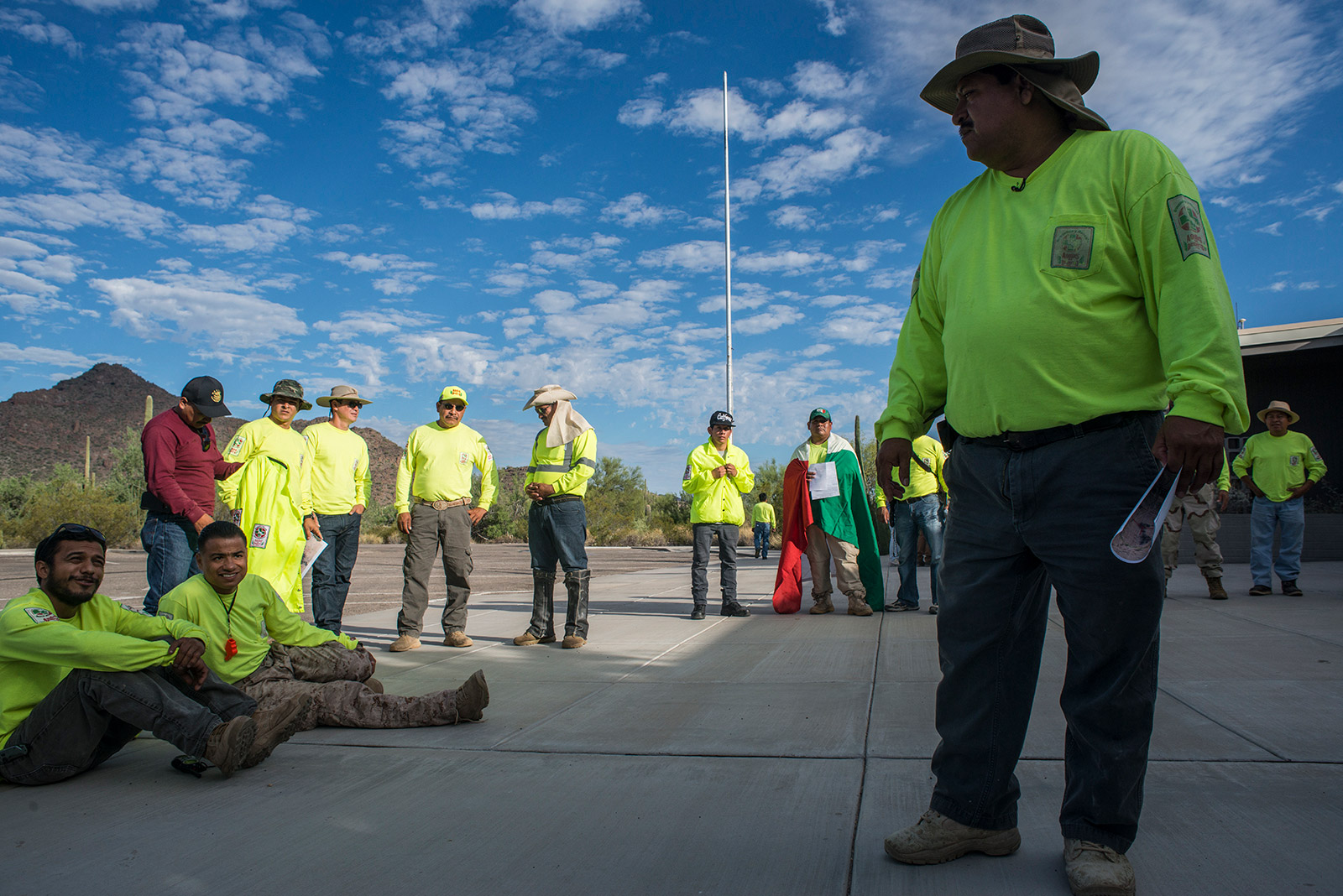 Ely Ortiz, founder and group leader of Aguilas Del Desierto, briefs his group of nearly two dozen volunteers at the visitors center of Organ Pipe Cactus National Monument in Arizona on Aug. 26, 2017. Members of the group wear neon yellow shirts so they are easily visible to one another as they search for lost migrants in the desert. <em>(Brandon Quester/inewsource)</em>
