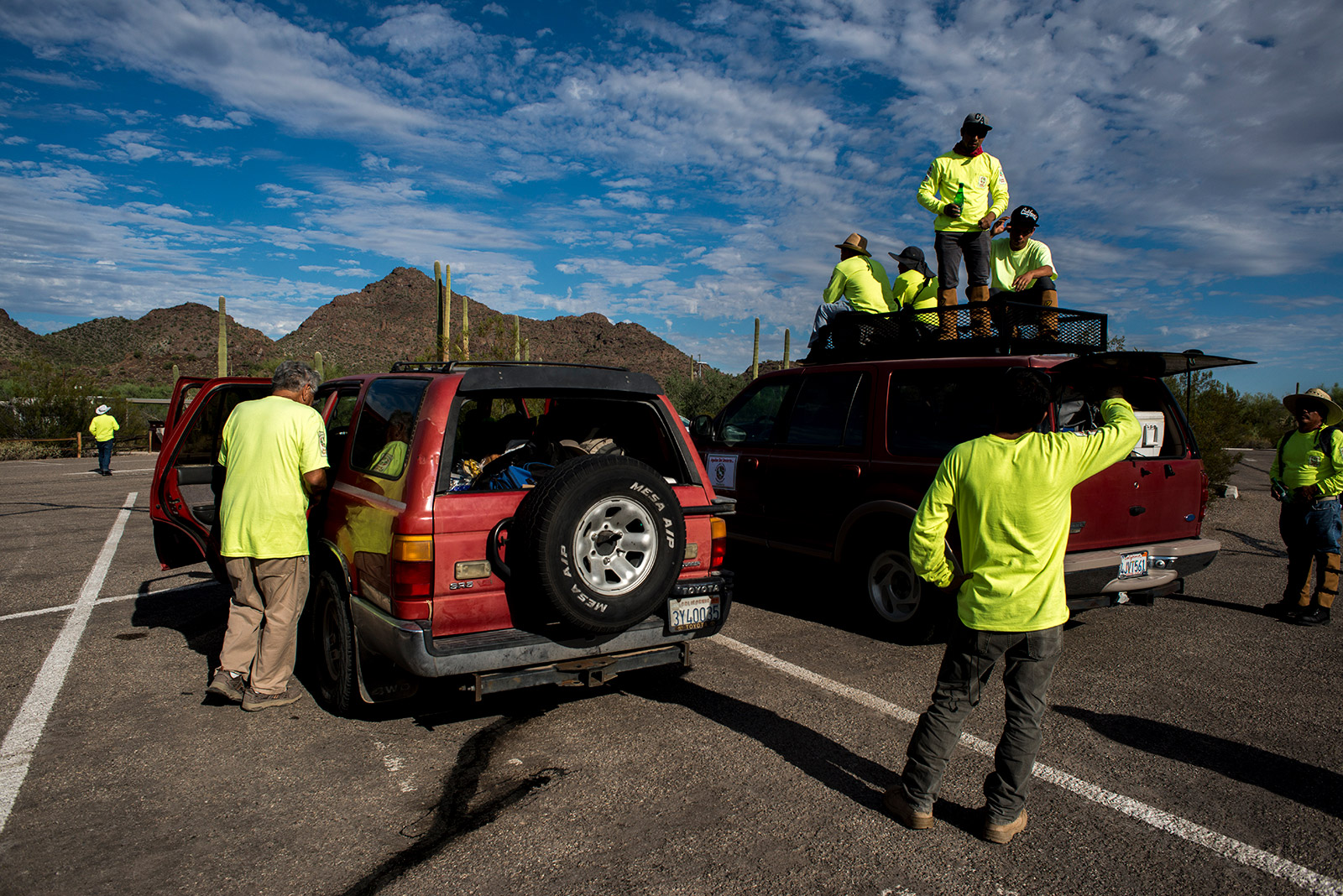 Volunteers with Aguilas Del Desierto load vehicles at Organ Pipe Cactus National Monument in Arizona before driving through the remote stretch of desert along the U.S.-Mexico border. Many of the volunteers wore snake-proof gaiters over their boots to protect themselves while searching for migrants in the desert on Aug. 26, 2017. <em>(Brandon Quester/inewsource)</em>