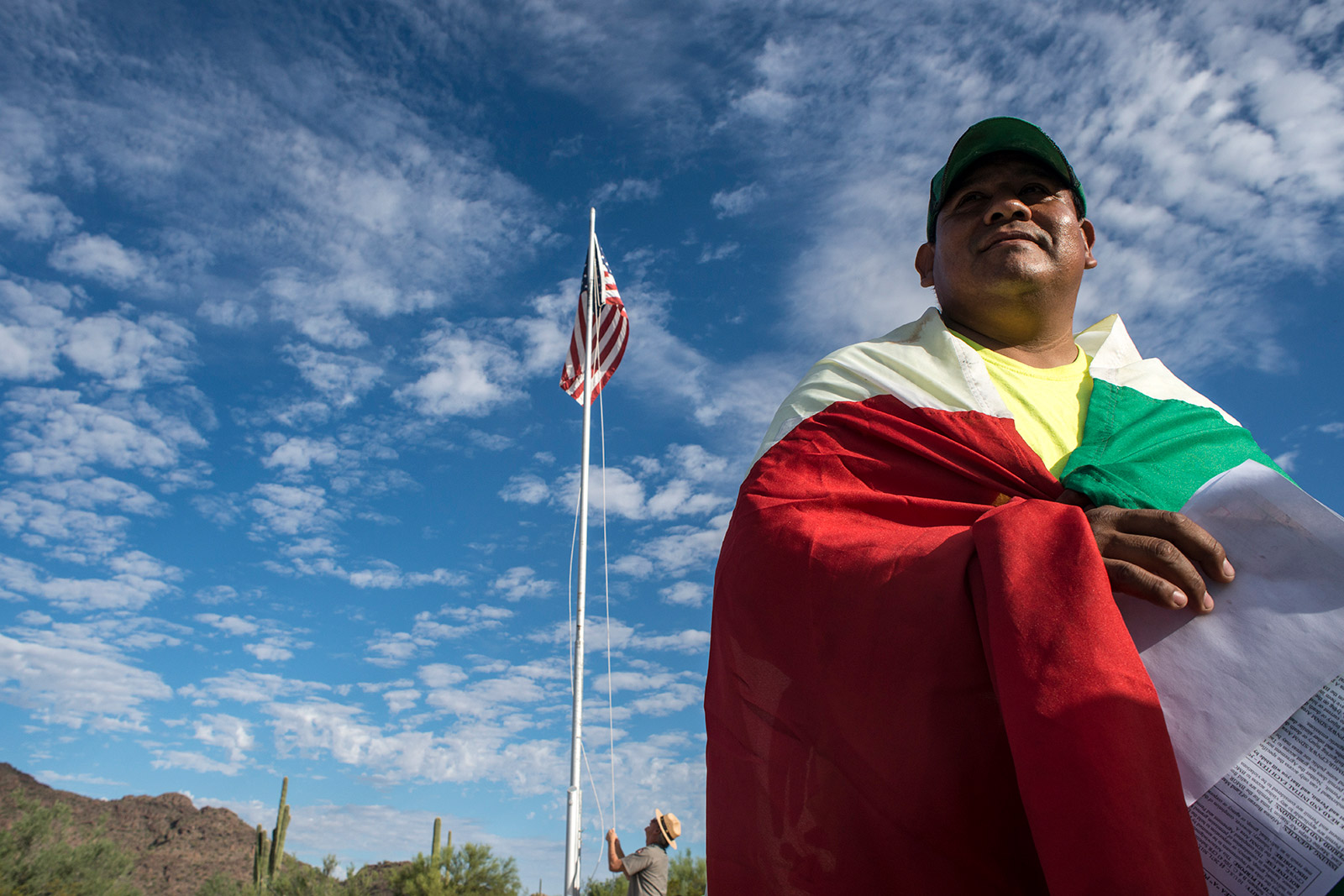 Aguilas Del Desierto volunteer Cesar Ortigoza listens to a safety briefing with a Mexico flag draped over his shoulders while standing outside the visitors center of Organ Pipe Cactus National Monument in Arizona on Aug. 26, 2017. <em>(Brandon Quester/inewsource)</em>