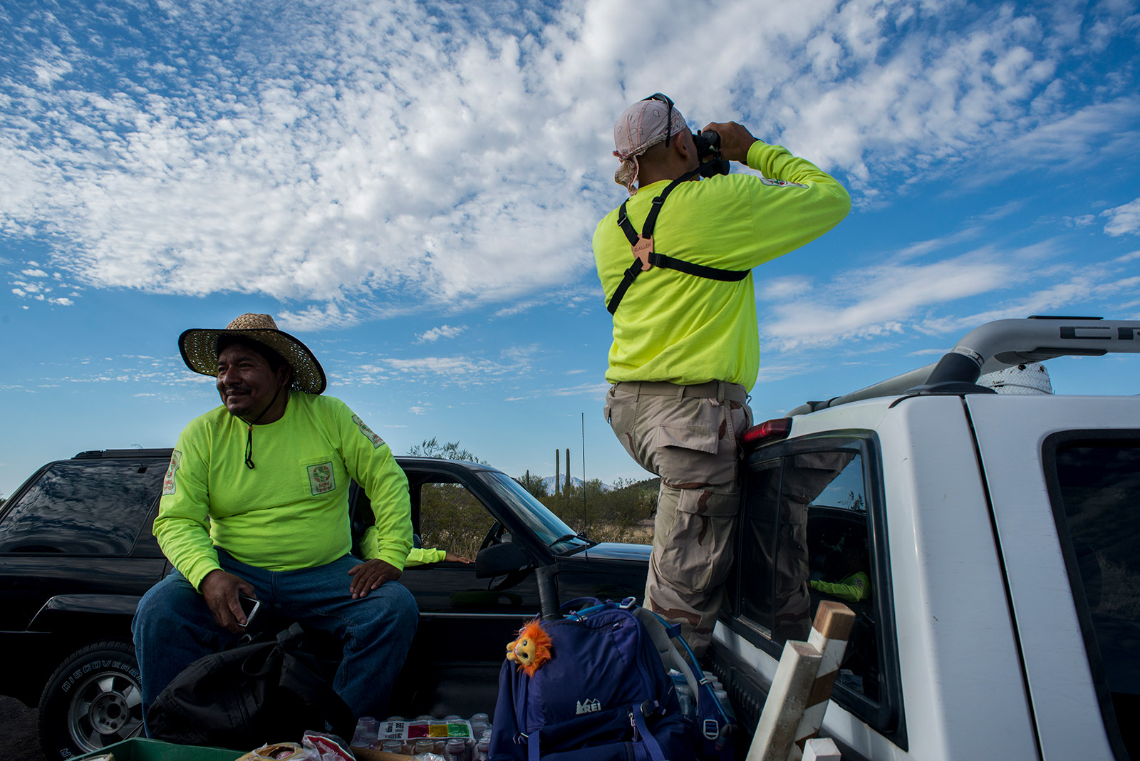 Julio Agustìn, left, waits in the back of a pickup as Pedro Fajardo peers into the desert with binoculars from the parking lot of the Organ Pipe Cactus National Monument visitors center in Arizona on Aug. 26, 2017. <em>(Brandon Quester/inewsource)</em>