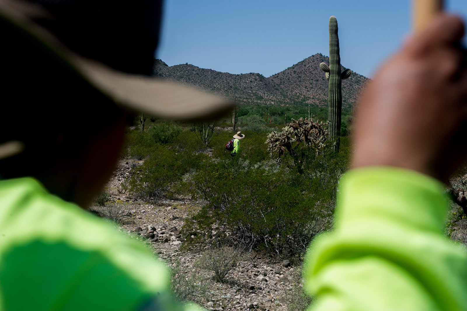 Ely Ortiz rests for a moment as one of his nearly two dozen volunteers walks nearby in the desert of Organ Pipe Cactus National Monument along the U.S.-Mexico border in Arizona on Aug. 26, 2017. <em>(Brandon Quester/inewsource)</em>