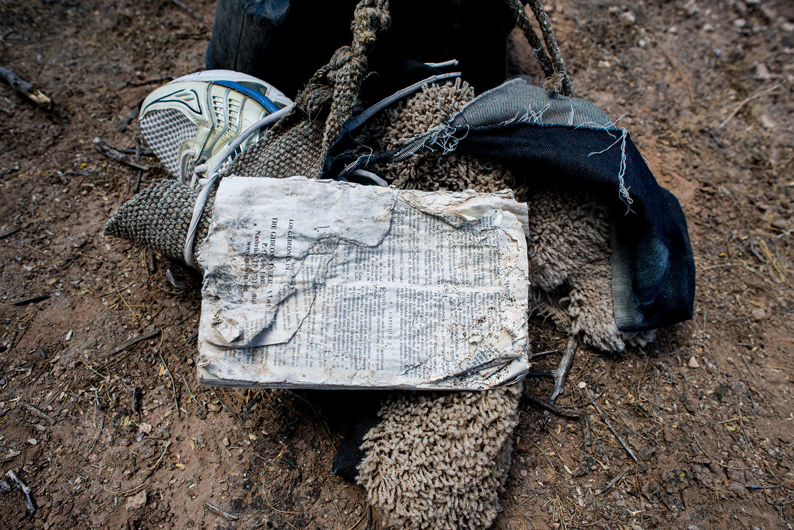 While searching for missing migrants in the Arizona desert on Aug. 26, 2017, volunteers from Aguilas Del Desierto collect discarded items including this Bible, shoes and carpet-like shoe covers that hide footprints. <em>(Brandon Quester/inewsource)</em>