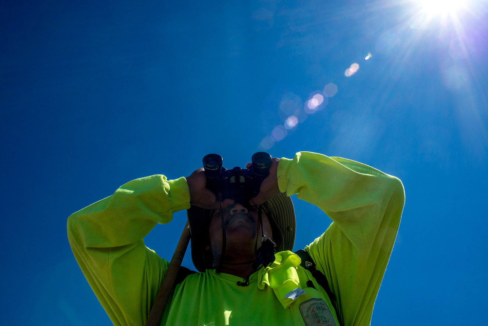 Ely Ortiz peers through his binoculars while scanning the desert along the U.S.-Mexico border in Arizona on Aug. 26, 2017. Wearing a long-sleeve shirt and hat, Ortiz and nearly two dozen volunteers walked through temperatures nearing 120 degrees while searching for missing migrants. <em>(Brandon Quester/inewsource)</em>