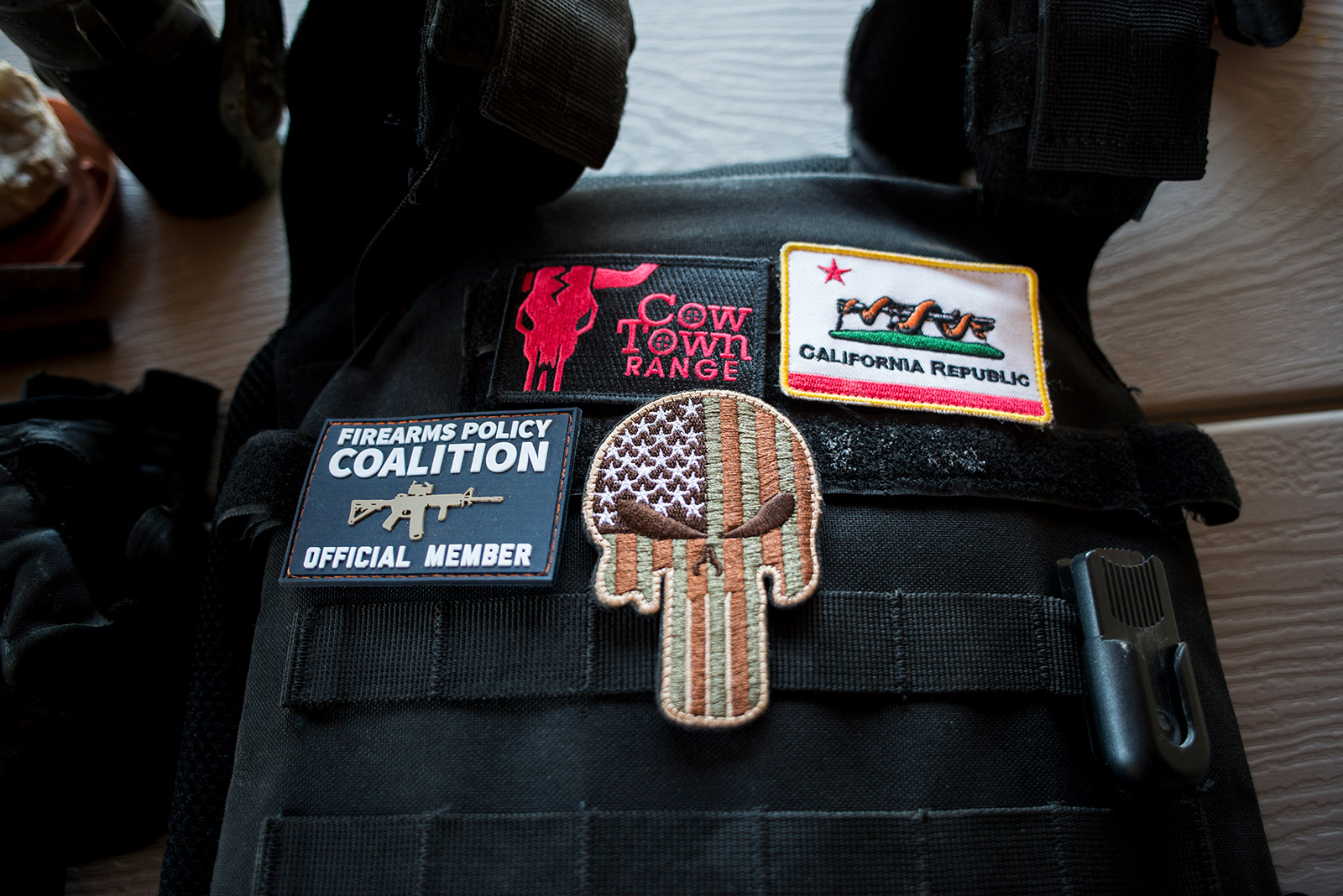 Bob Maupin's bulletproof vest is adorned with patches, including an American flag in the outline of a skull, which symbolizes a comic book character known as the Punisher – a vigilante who takes matters of the law into his own hands. Maupin wore this vest, a side pistol and a rifle while patrolling his property in the eastern San Diego County community of Boulevard on Aug. 30, 2017. <em>(Brandon Quester/inewsource)</em>