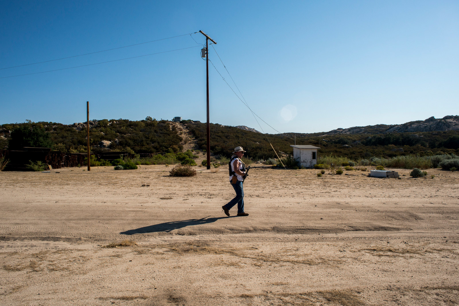 Bob Maupin, 78, walks along a dirt road on his property that leads from his home to the U.S.-Mexico border. Maupin carries a rifle, pistol and wears a bulletproof vest while walking his property on Aug. 30, 2017. <em>(Brandon Quester/inewsource)</em>