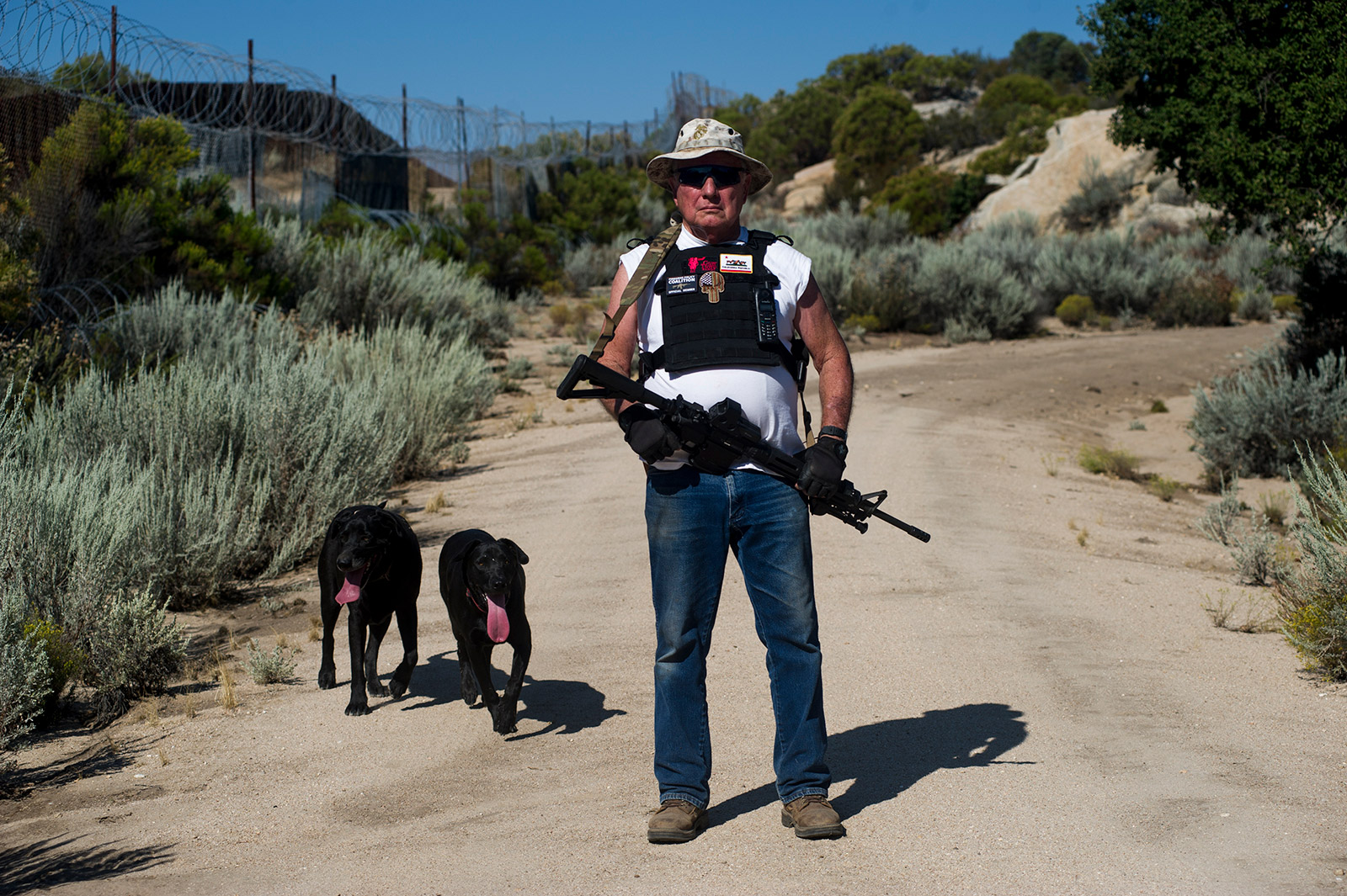 Bob Maupin, 78, poses on Aug. 30, 2017, for a portrait with his dogs Shadow and Inky while patrolling his ranch that borders Mexico. Maupin erected his own 10-foot-high fence, including razor wire at the top, which took him five years to build. <em>(Brandon Quester/inewsource)</em>