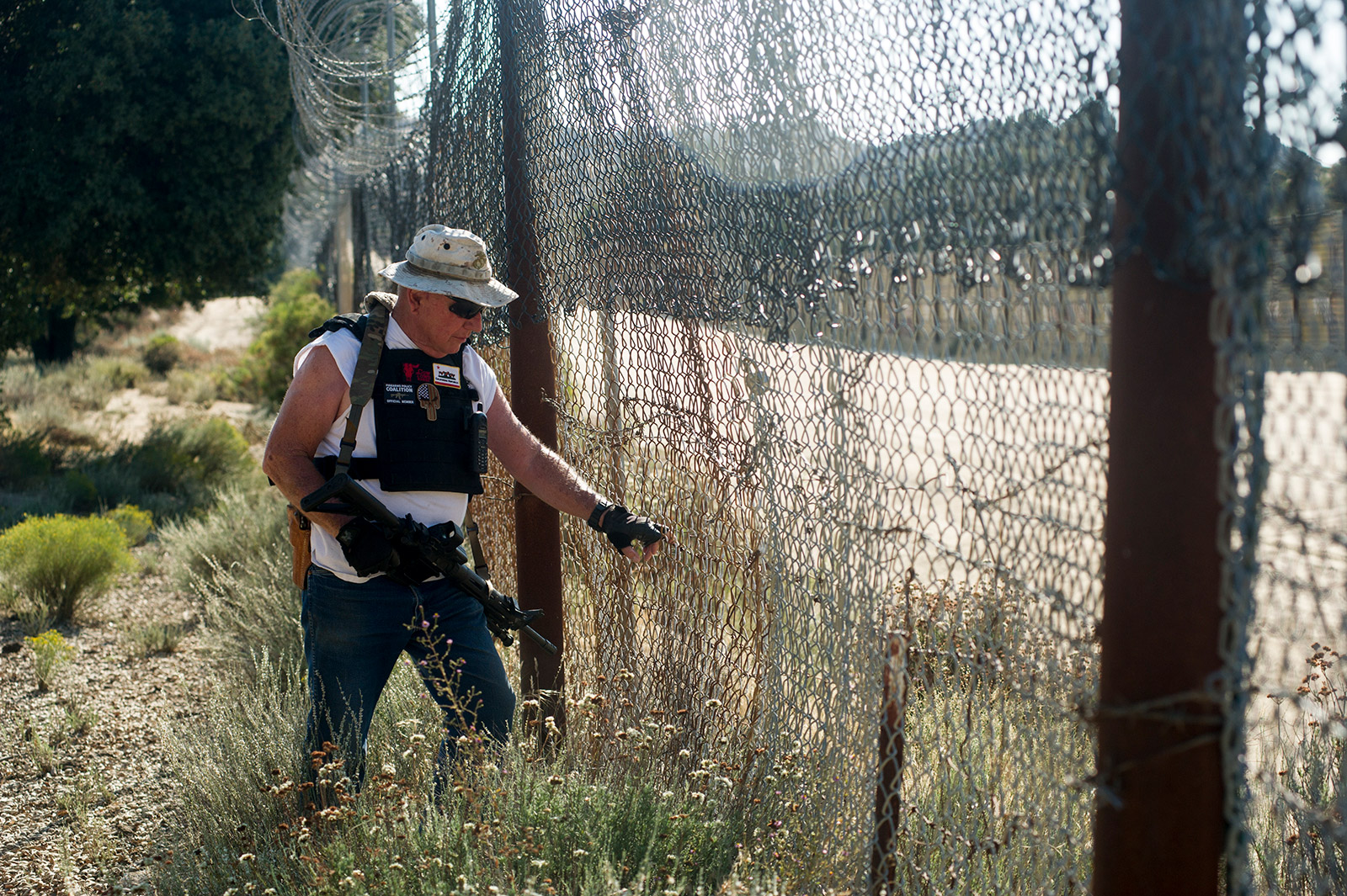 Bob Maupin, 78, checks an area of fencing along the U.S.-Mexico border at his ranch outside Boulevard in eastern San Diego County. Maupin said drug and human smugglers often cut through his fence to enter the U.S. illegally. This photo is from Aug. 30, 2017. <em>(Brandon Quester/inewsource)</em>