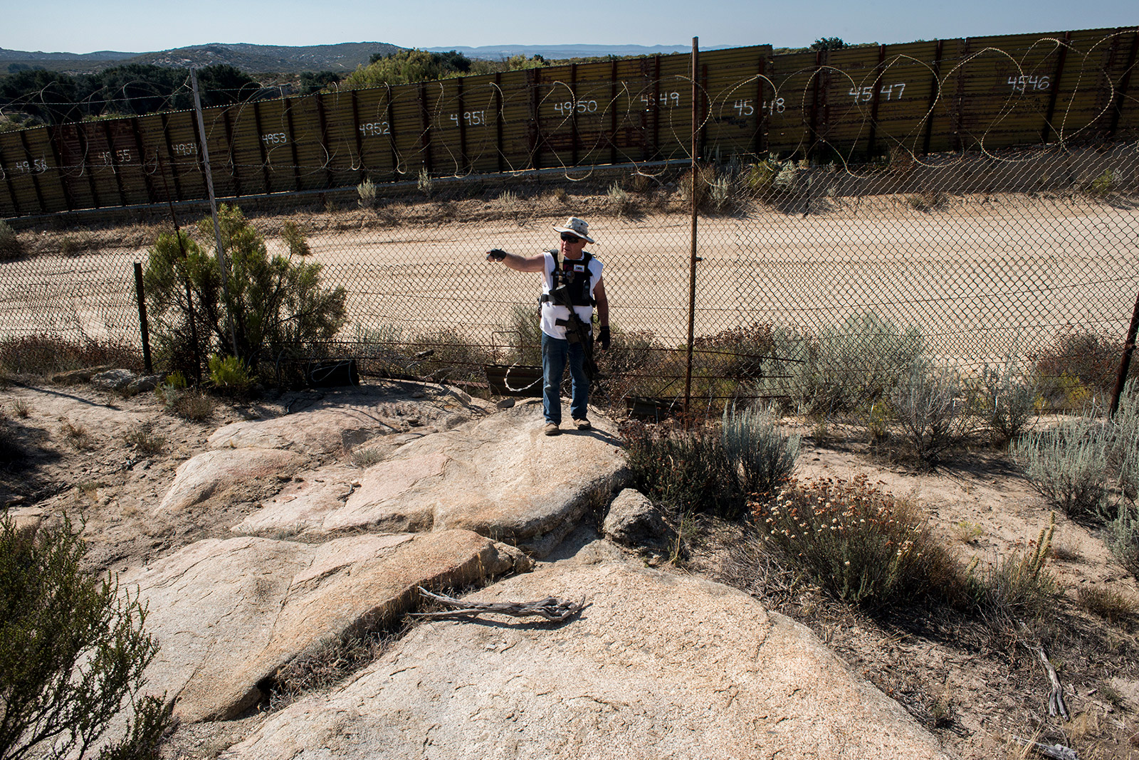 The only barrier between Bob Maupin's 250-acre ranch in Boulevard and Mexico is corrugated steel built by the government and a 10-foot-tall barbed wire fence that he built over five years. Maupin, shown on Aug. 30, 2017, patrolling his land with a weapon in-hand, said drug and human smugglers often cut through the fencing to enter the U.S. illegally. <em>(Brandon Quester/inewsource)</em>
