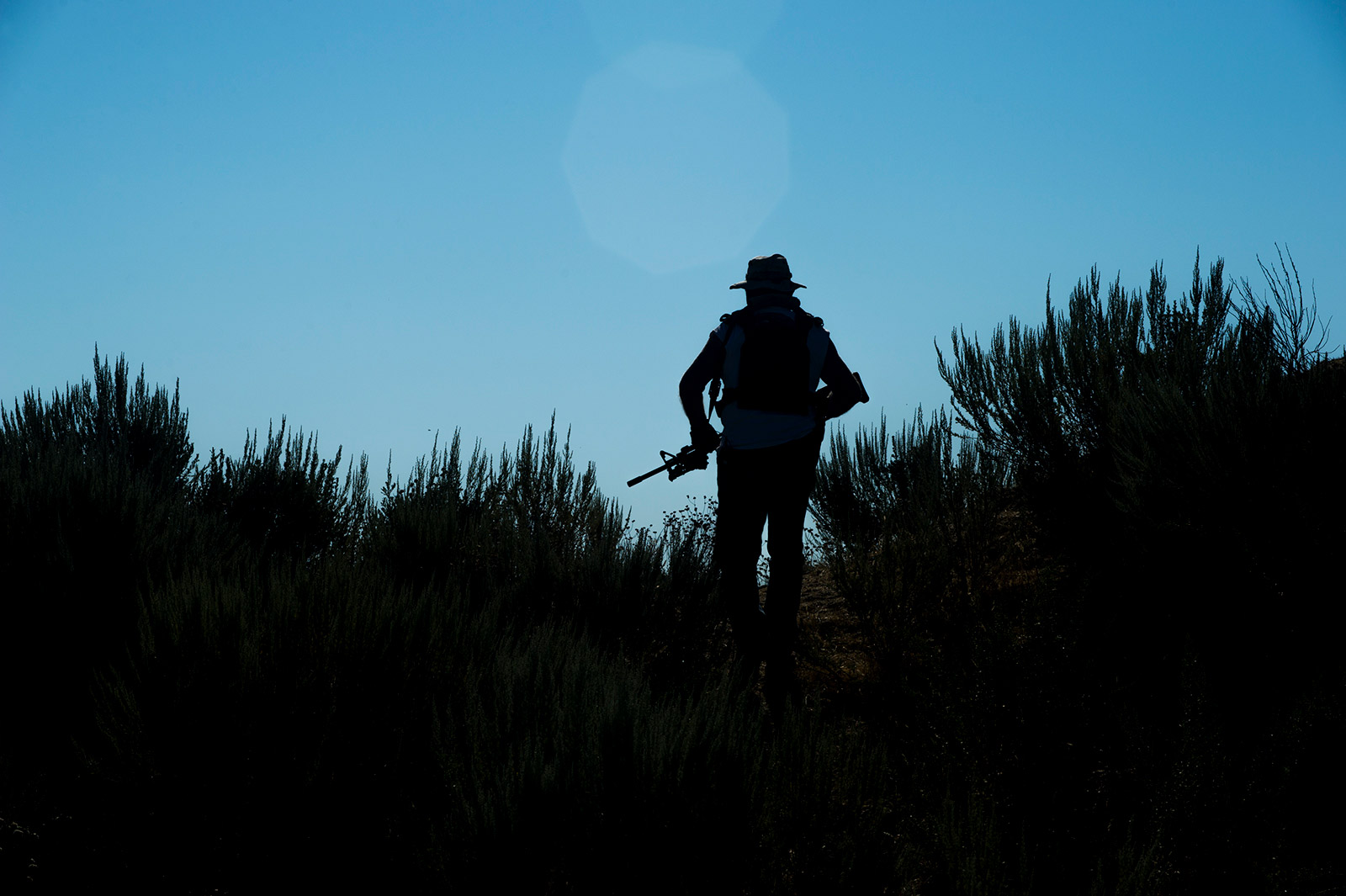 Cresting a small hill on his 250-acre ranch along the U.S.-Mexico border, 78-year-old Bob Maupin of Boulevard is silhouetted with his AR-10, or ArmaLite Rifle. This photo is from Aug. 30, 2017. <em>(Brandon Quester/inewsource)</em>